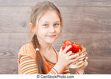 child holding a wicker basket with tomatoes