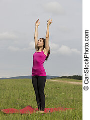 Woman doing sun salutation in yoga outdoors - Young woman is...