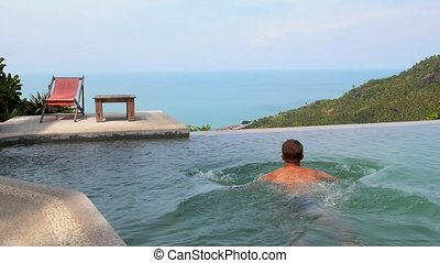 Man Relaxing and Swimming in Endless Luxurious Pool - Tanned...