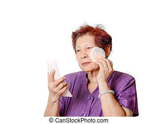portrait of beautiful mature woman applying make up
