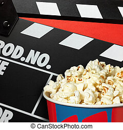 Clapper board and popcorn box on red background