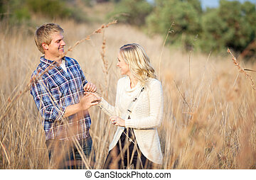 Young couple playing in tall grass - Young Caucasian couple...
