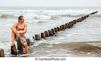 Middle-aged man sitting near the sea and looking...