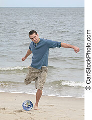 soccer player on the beach - one young athletic man with a...