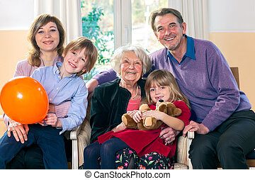 Family posing with grandma smiling and looking happy