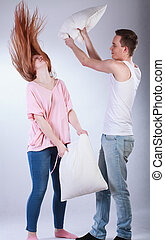 Young couple having pillow fight on isolated grey background