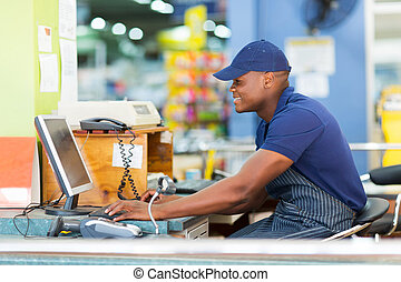 african male cashier working at till point - happy african...