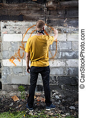 Male hooligan painting graffiti - Vertical view of male...