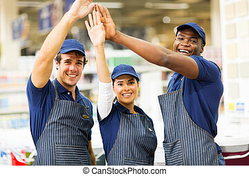 group of hardware store workers high five - group of...