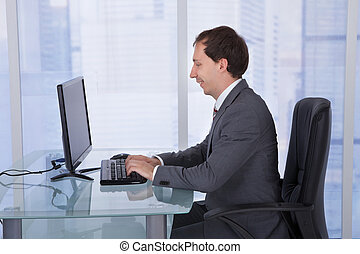 Businessman Working On Computer At Desk In Office