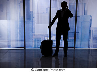 Businessman With Luggage Using Cell Phone In Office - Full...