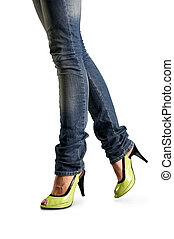 Female feet in jeans and in green shoes