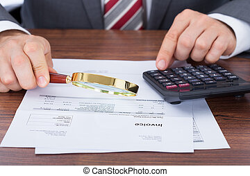Businessman Calculating Invoice While Holding Magnifying...