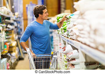 young man shopping in hardware store - young man shopping...