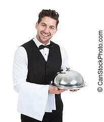 Confident Waiter Holding Domed Tray - Portrait of confident...