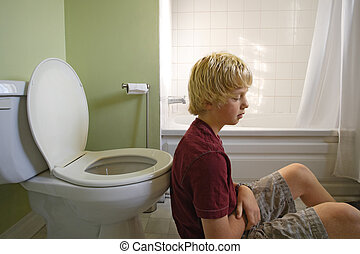 Feeling sick - A young boy suffering with a stomachache,...