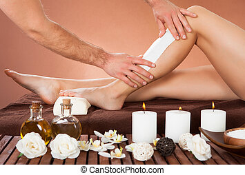 Therapist Waxing Customers Leg At Beauty Spa - Cropped image...