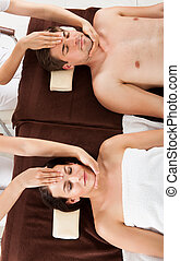 Relaxed Couple Receiving Head Massage At Beauty Spa - High...