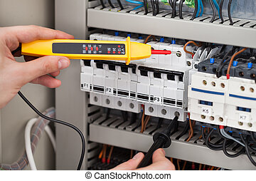 Electrician Examining Fusebox With Voltage Tester - Cropped...