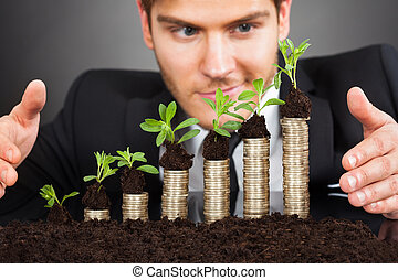 Businessman Protecting Coins In Saplings - Young businessman...