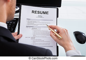 Businessman Analyzing Resume At Office Desk - Cropped image...