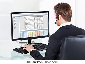 Businessman In Headset Using Computer At Desk - Rear view of...