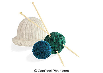 Two balls of wool with knitting needles and cap isolated on...