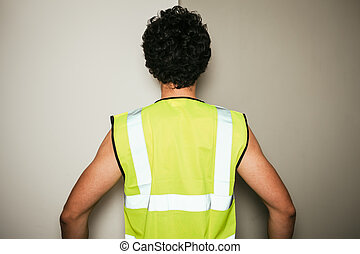 Rear view of builder in high visibility vest - Rear view of...