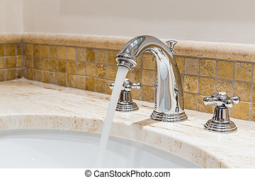 Modern water tap in the bathroom. Flowing water.