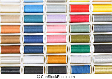 Sewing threads vivid multiple colors in box, isolated on...