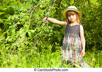 Little girl posing in a straw hat in the park.