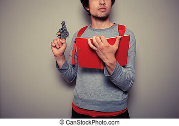Student with gun and book - A Young student is holding a red...