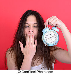 Portrait of sleepy young female in chaos holding clock...