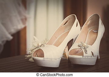 bridal shoes - a pair of wedding shoes on wooden table