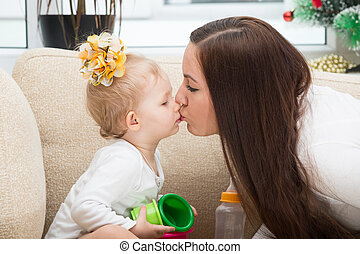 Happy mom and child girl hugging and kissing at home The...
