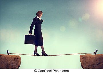 businesswoman balancing on a tightrope conquering adversity...