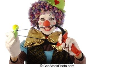 the clown and the slingshot - A bumbling clown using a...