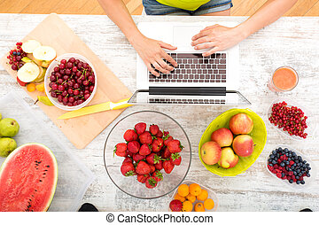 Researching Fruits - A beautiful mature woman using a Laptop...