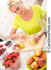 Mature woman preparing a smoothie