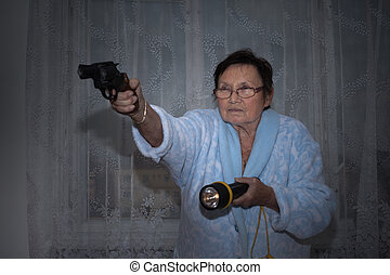 Senior woman with a gun and torch - Scared senior woman...