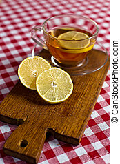 lemon on a wood board and cup of tea - sliced lemon on a...