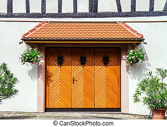 Renovated wooden garage doors in old house, Alsace, France