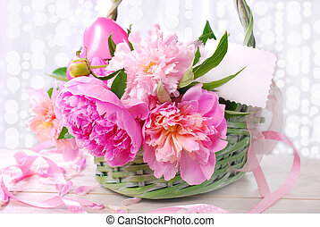 beautiful pink peony in wicker basket with blanc card...