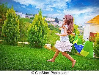 Happy football fan, cute little girl running on backyard...