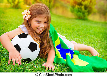 Young cheerful football fan lying down on fresh green grass...