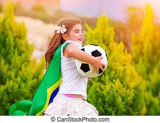 Little active football fan running on the green grass field...