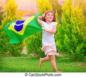 Happy little football fan, cute little girl running on the...