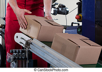 Worker putting a box on conveyor belt - Close-up of worker...