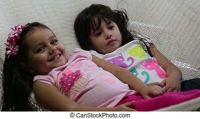 Adorable little girls lying in hammock