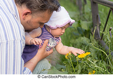 discoveries - father holding baby studying yellow spring...